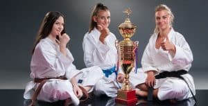 Martial Arts Lessons for Kids in Orlando FL - Thumbs Up and Trophies with Sitting Girls